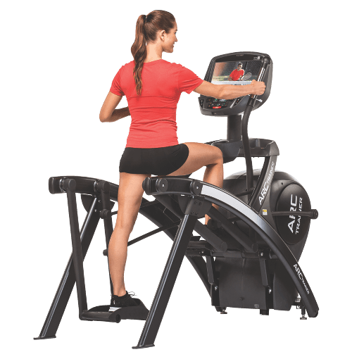 a woman using a Cybex 525 AT Arc Trainer